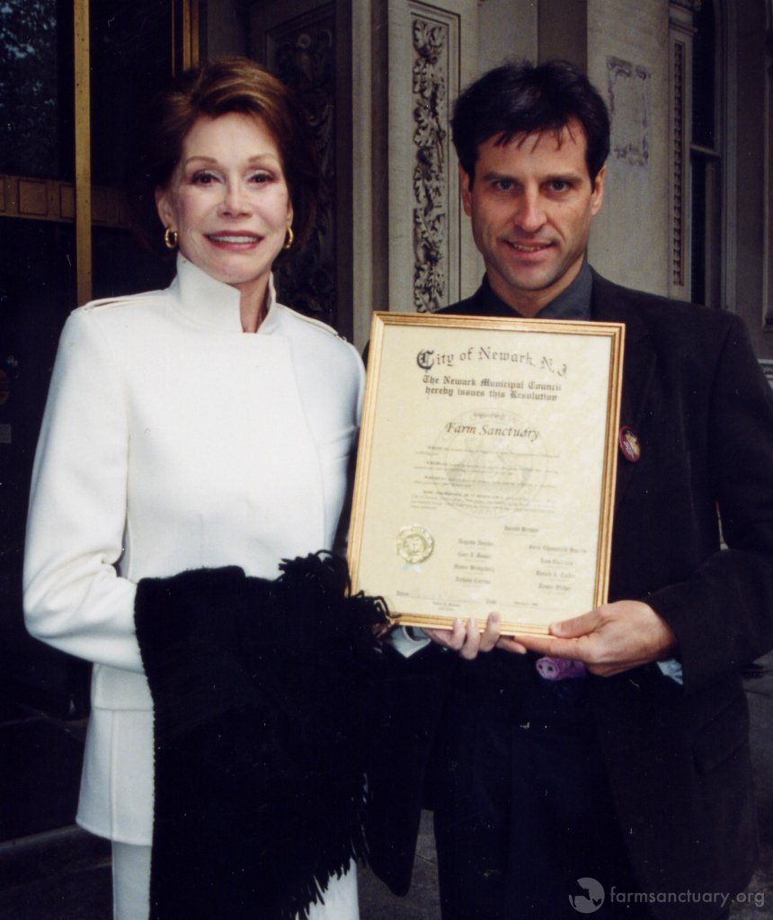 Mary Tyler Moore and Gene Baur hold a resolution from the City of Newark, NJ.